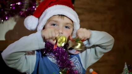 Boy playing with Christmas toys and bells