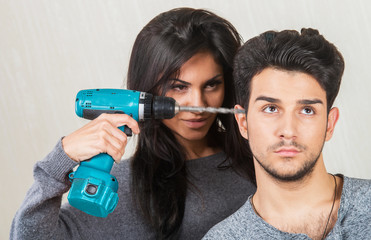 Annoyed woman drilling into her boyfriend's head