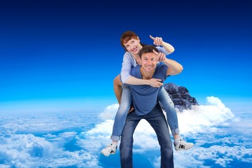 Composite image of man giving girl a piggy back