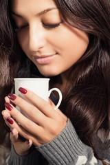 Портрет красивой женщины с чашкой горячего напитка в руках.