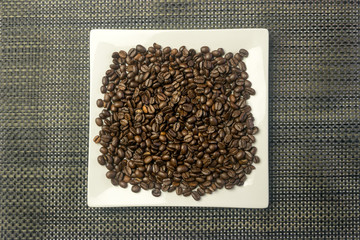 White square plate with a heap of coffee beans