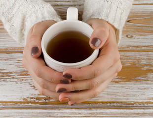 Woman holding hot cup of tea over  a white wooden background