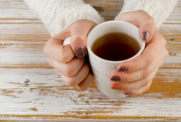 Woman holding hot cup of tea over    wooden background