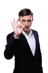 Happy young businessman gesturing OK sign over white background