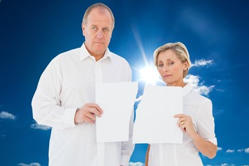 Composite image of upset couple holding torn piece of paper