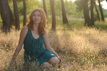 Portrait of a beautiful red-haired girl sitting in the grass