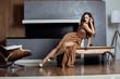 beauty yong brunette woman sitting near fireplace at home,
