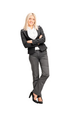 Young businesswoman leaning against a wall