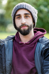 Portrait of trendy guy wearing hat in park at winter