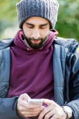 Portrait of trendy guy wearing hat and using a mobile in park at