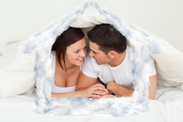 Composite image of happy couple hiding under a blanket