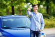 Young man holding key of his new car
