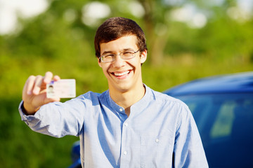 Happy young man showing his driving license