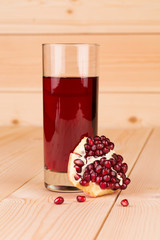 Glass of pomegranate juice and grains on wood.