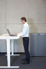 Businessman with eyeglasses standing at  height adjustment table