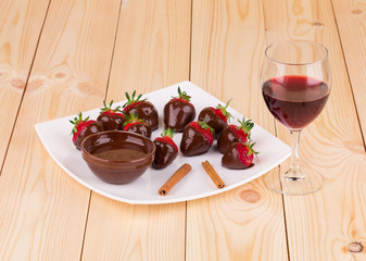 Strawberries in chocolate with cinnamon on wood.