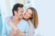 Middle-aged couple embracing in front of house - 74720863