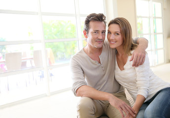 Romantic middle-aged couple sitting on couch