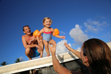 Little girl jumping from pontoon to mother's arms