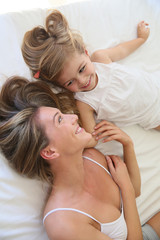Mother and daughter playing in bed in morning time