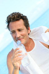 Handsome man drinking water from bottle after exercising