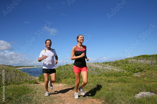 canvas print picture Couple running by the sea on track