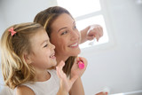 Fototapety Mother and daughter in bathroom brushing her teeth