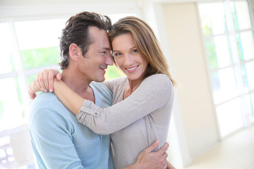 Cheerful 40-year-old couple embracing in home living-room