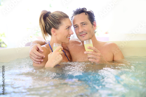 Romantic couple drinking cahmpagne in hot tub - 74721050