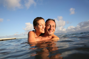 Couple swimming in sea at sunset