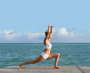 Woman doing stretching exercises in pontoon by the sea