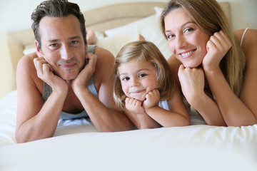 Portrait of happy family of three laying on bed