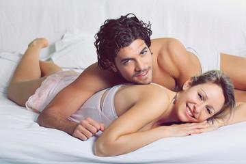 Joyful couple smiling in bed