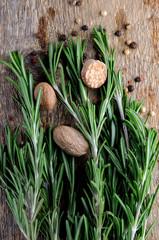 pepper, ground nutmeg and rosemary on dark wooden background