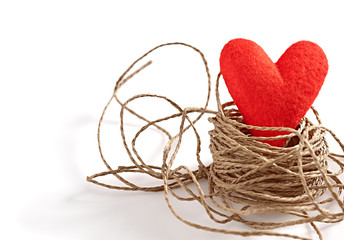Valentines Day. Red handmade heart in nest of twine