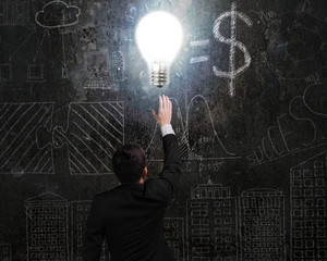 businessman touching brightly light bulb illuminated dark doodle