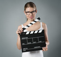 Pretty woman holding clapperboard. Film production concept