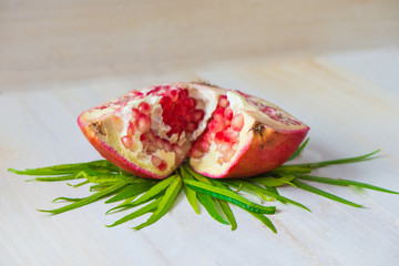 Juicy pomegranate and its half with leaves