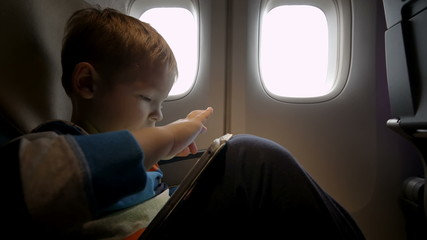 Little boy playing on touch pad in the plane