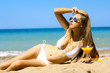 canvas print picture - beautiful girl with orange juice posing on the sandy beach