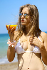 beautiful girl with orange juice posing on the sandy beach