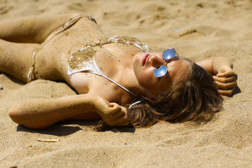 beautiful girl in sunglasses posing on beach sand