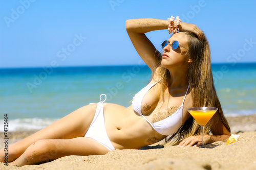 canvas print picture beautiful girl with orange juice posing on the sandy beach