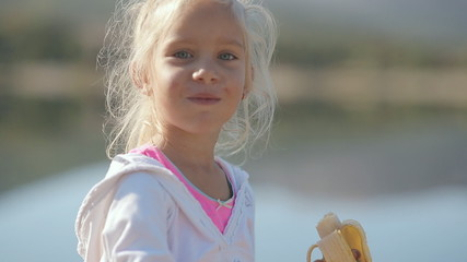 Little blond girl eating a banana next to the lake shore