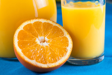Orange juice in jar and glas with fruit slice