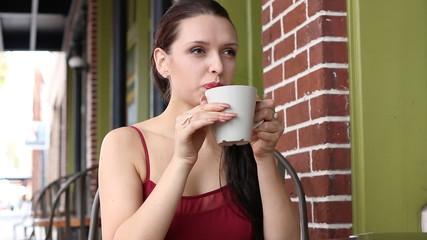 Beautiful latvian woman drinking latte at cafe