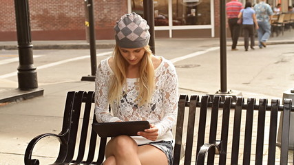 Beautiful hipster girl using touchpad tablet outdoors