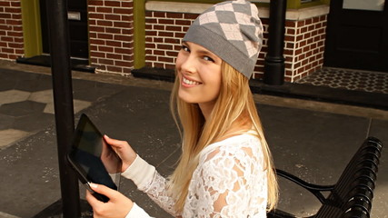 Smiling hipster blond woman using digtial  tablet on city street