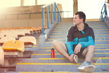 sportsman sitting with bottle of water on stairs on the stadium