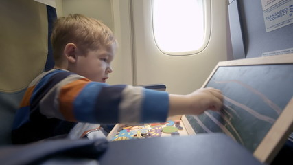 Boy in the plane drawing on board with chalk